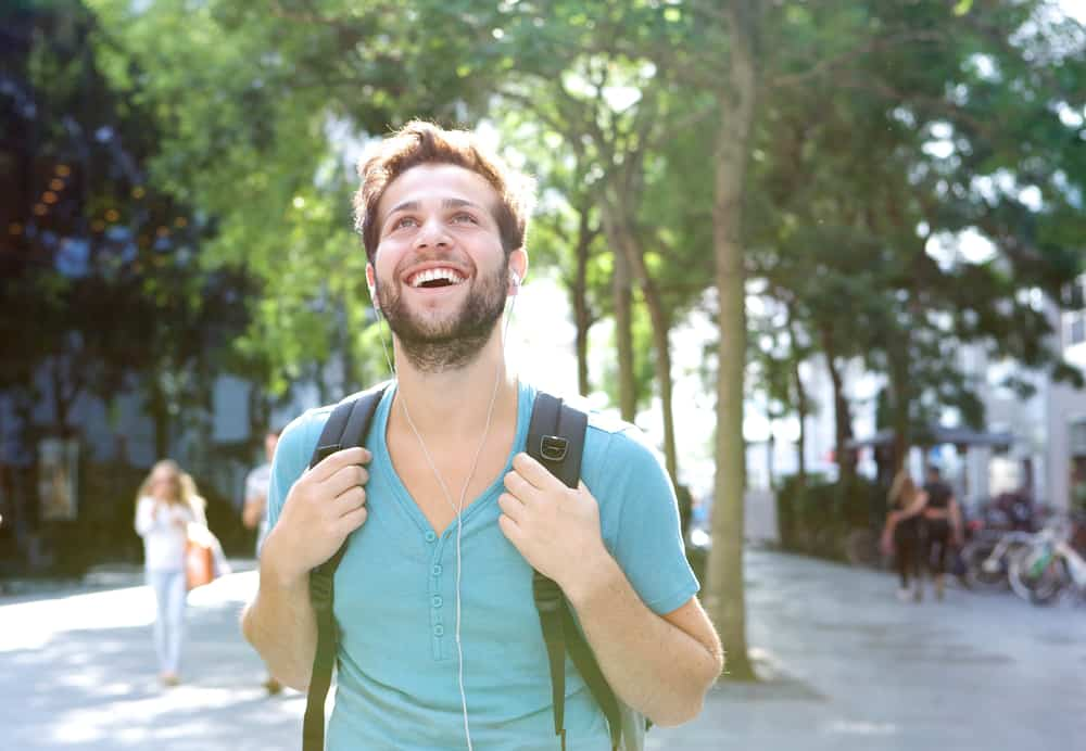 Close up portrait of a handsome young man walking outdoors with backpack