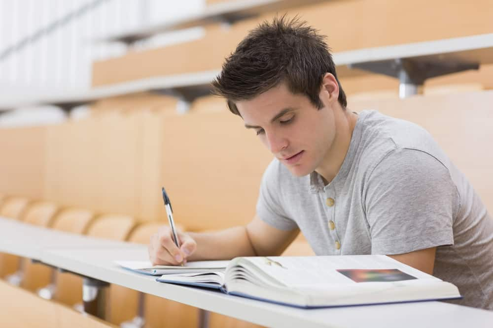Student taking notes in lecture hall